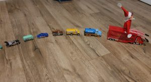 elf-on-the-shelf-riding-line-of-cars